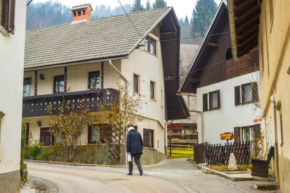 old lady carrying milk pail past alpine houses