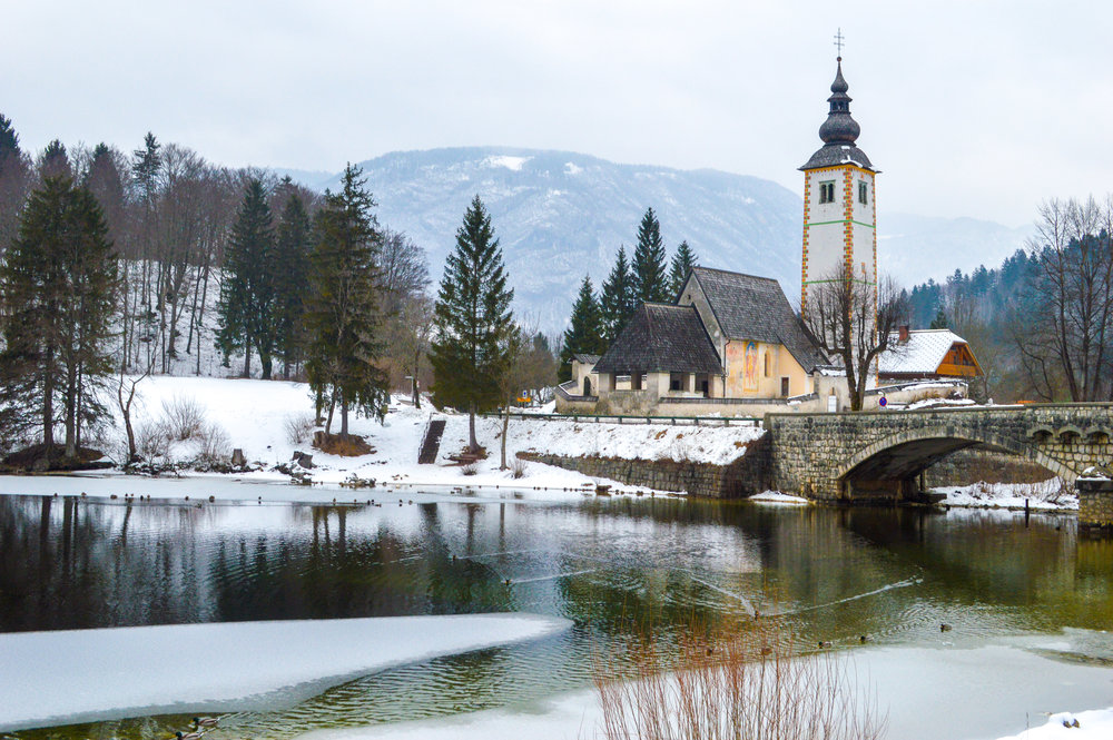 frozen stream with church and pine trees - is Slovenia worth visiting?