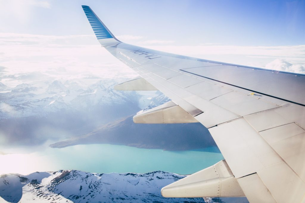 aeroplane wing with mountains and lake