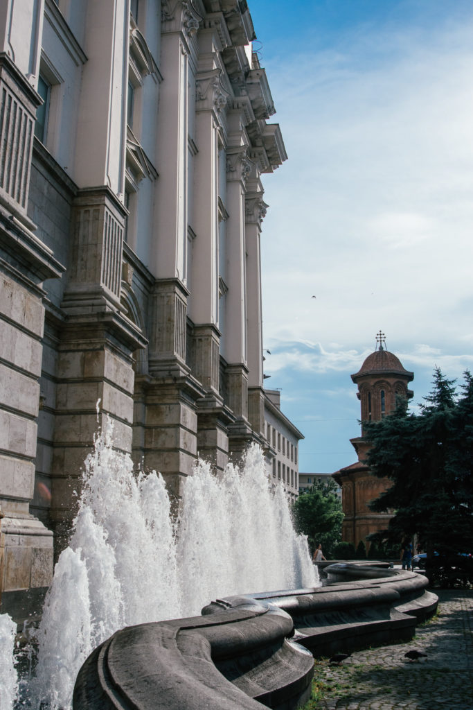 a water fountain in front of a grand building in Bucharest