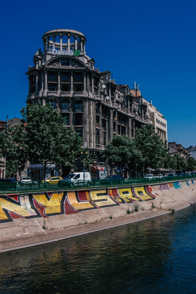 graffiti and grand building in front of Bucharests river