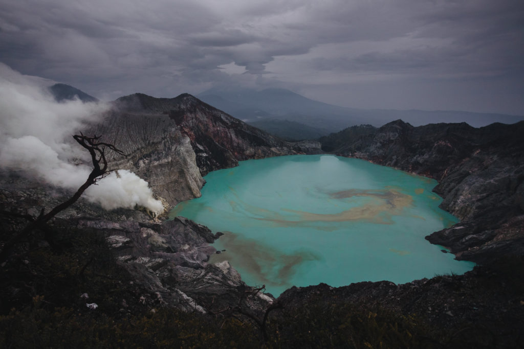 blue lake in black crater with white steam