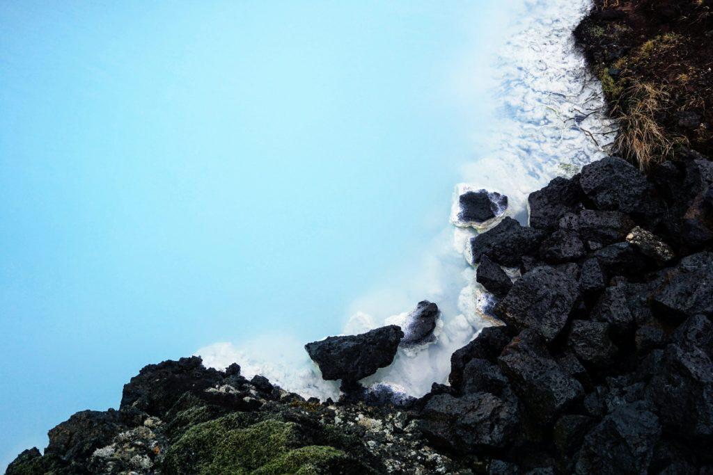 milky blue lagoon water next to black rocks