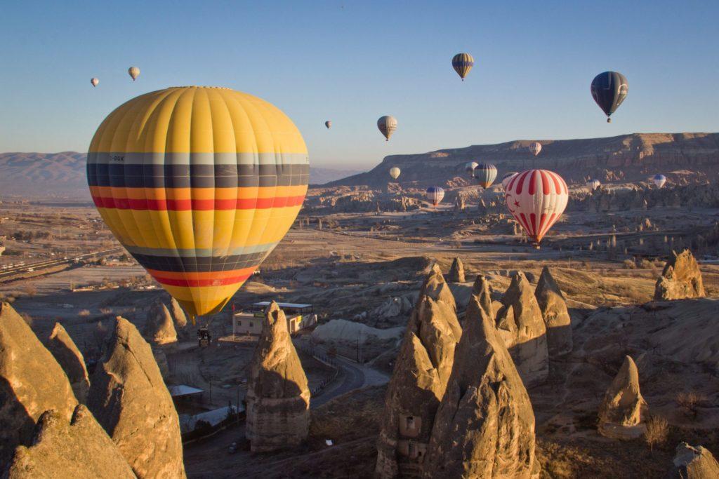 hot air balloons over rocky outcrops