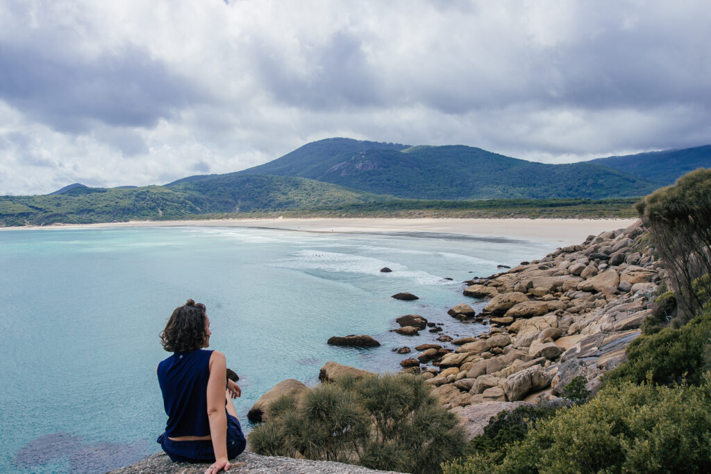 girl sat on rock overlooking sea at Wilsons Prom
