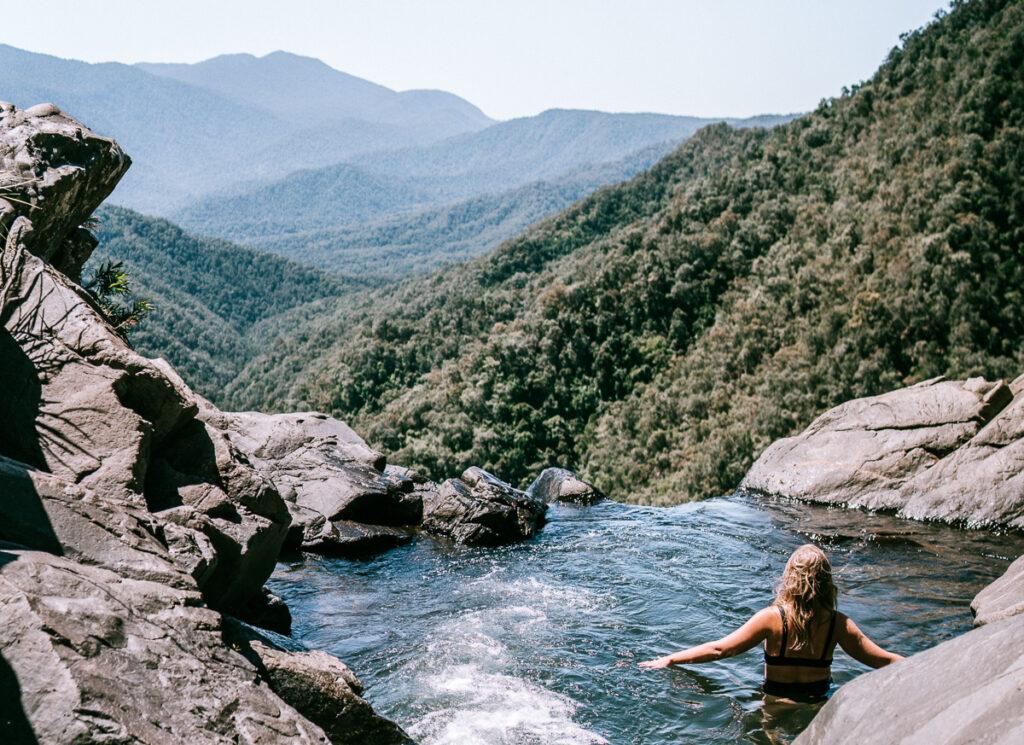 girl in waterfall rock pool overlooking mountains