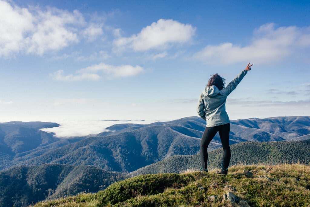 girl standing on top of mountain with arm up in the air with peace sign