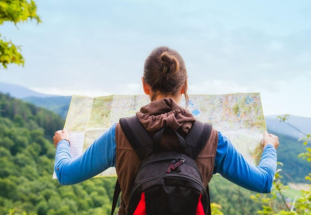 girl holding map whilst hiking alone