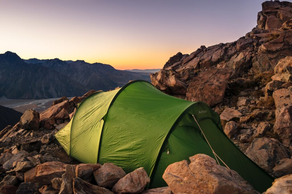 green tent set amongst rocks