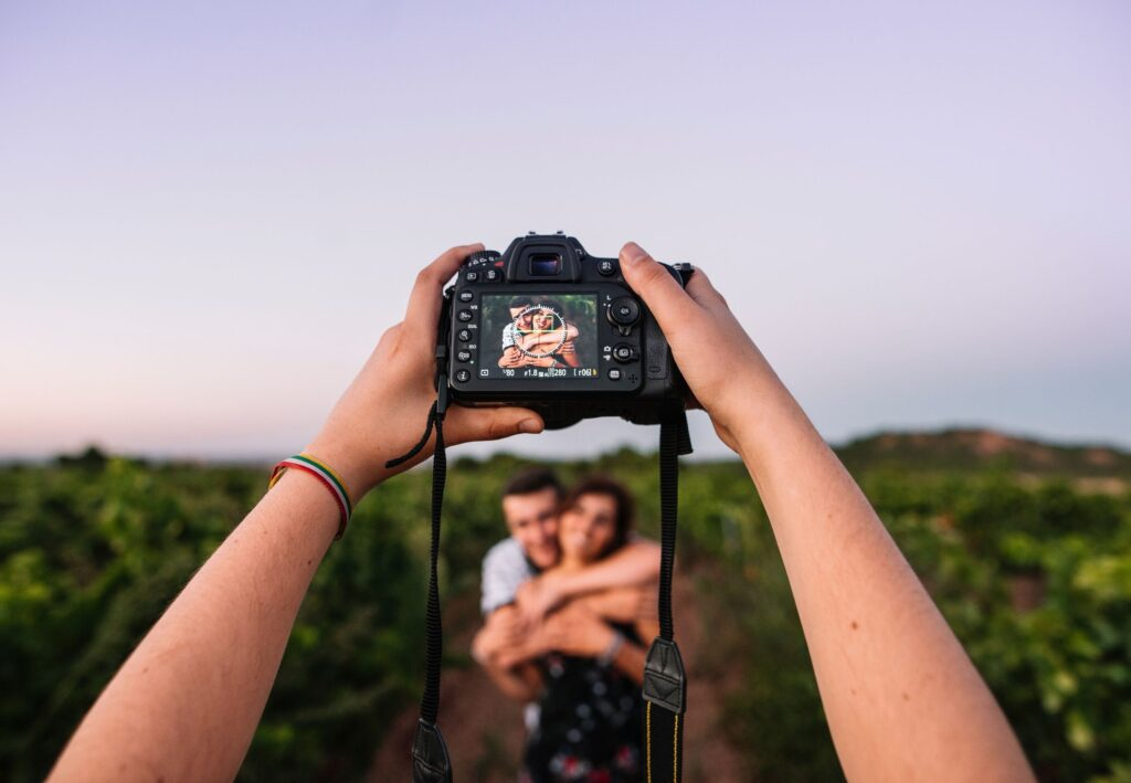 hand holding camera with couple having a photoshoot