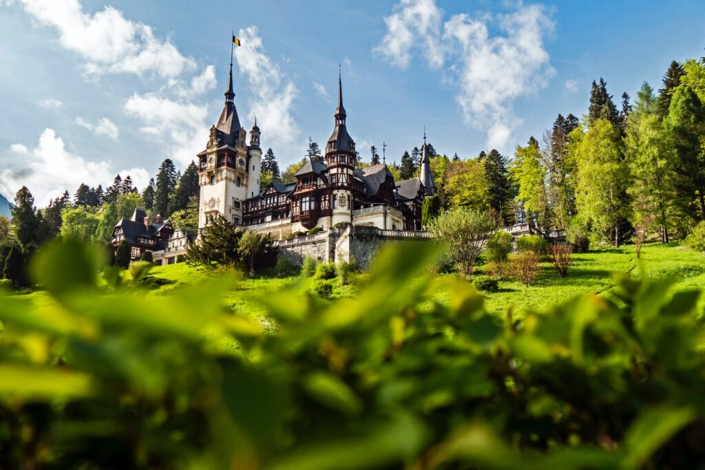 A castle in Romania surrounded by green shubbery