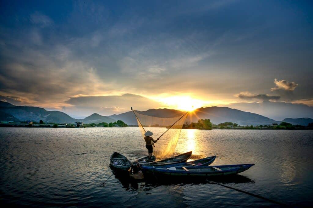 fisherman throwing net at sunset in vietnam
